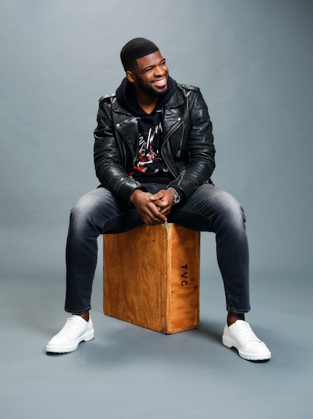 P.K. Subban wearing black leather jacket and hoodie with jeans sitting on box