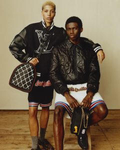 Two men, one standing with blonde hair, wearing a Louis Vuitton bomber jacket, shorts, and duffle bag. The other man sits on a stool and wears a quilted Louis Vuitton parka, white sports shorts and holds a small LV bag.