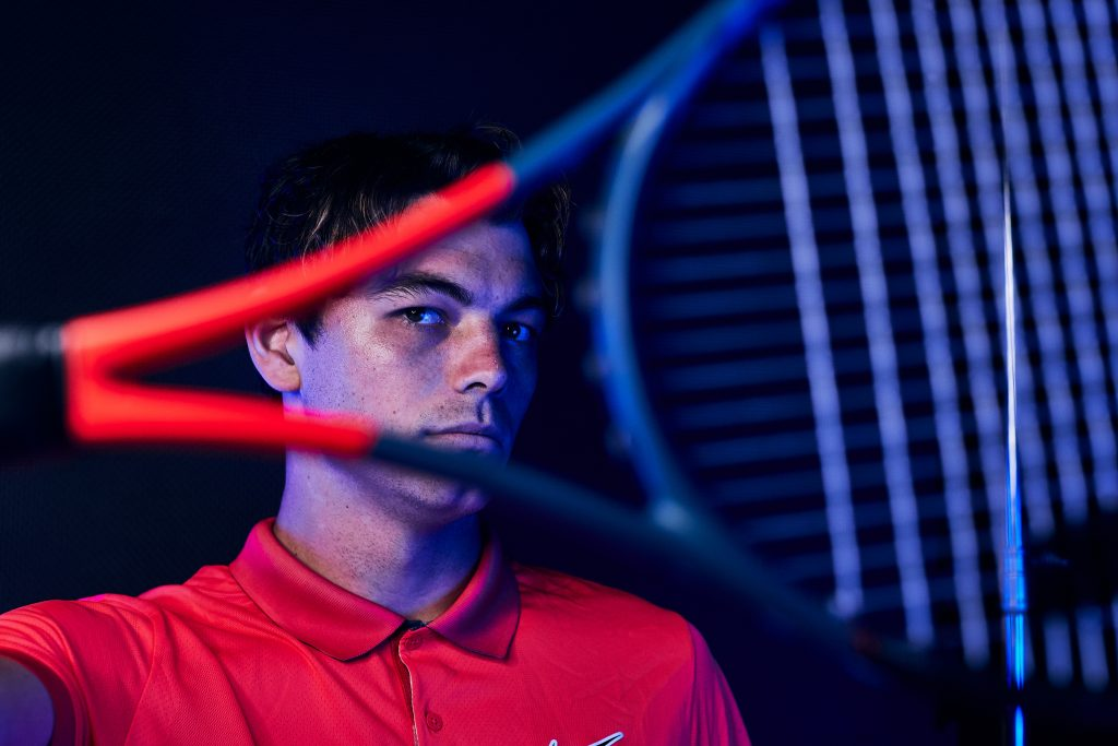 Taylor Fritz in red polo holding tennis racquet