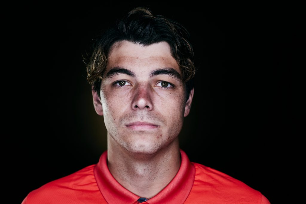 Taylor Fritz wearing red polo with black background
