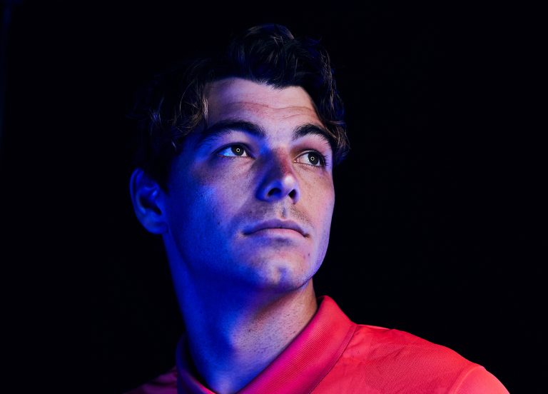 Taylor Fritz in red polo looking up